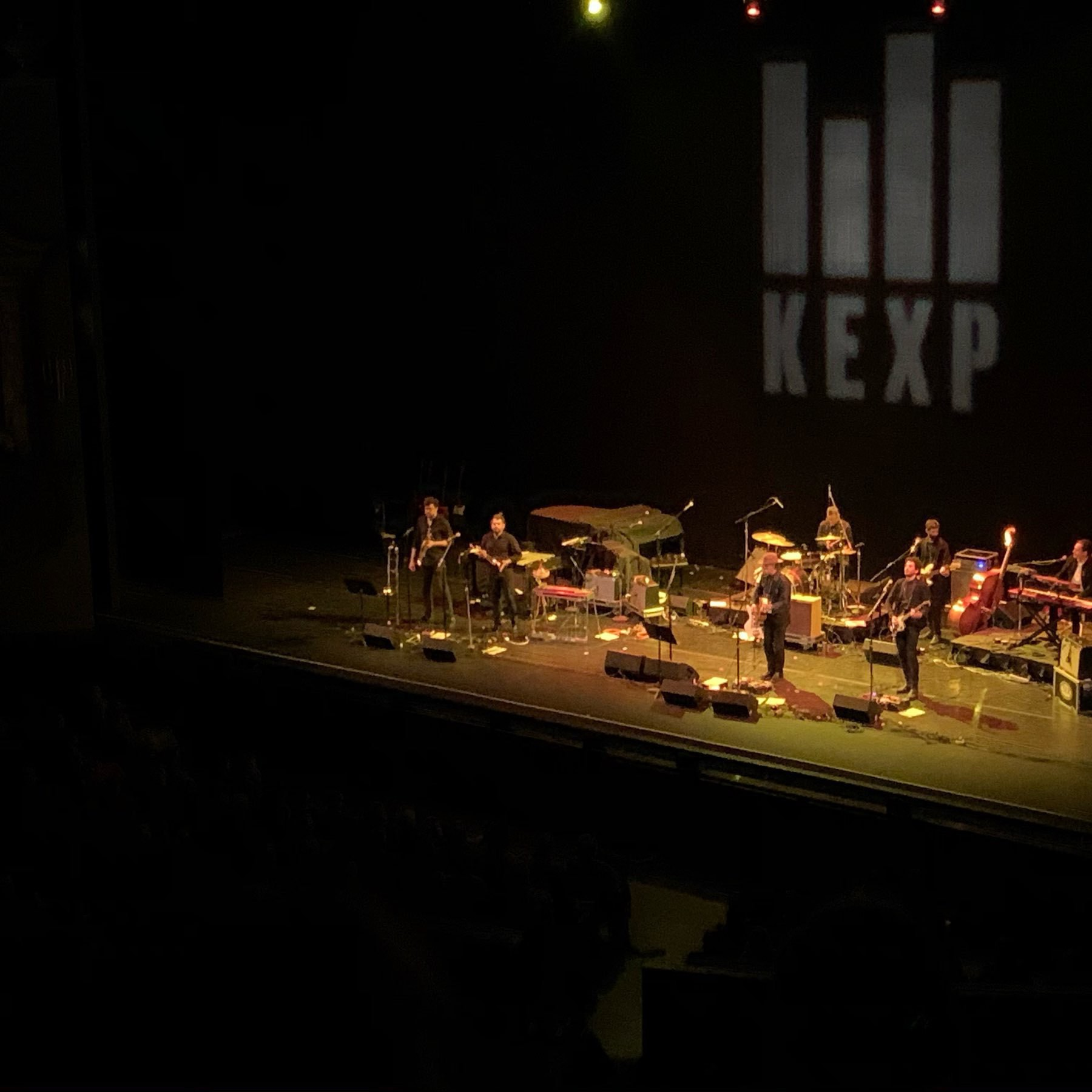 Calexico performing on stage, projected on the backdrop is the KEXP FM logo