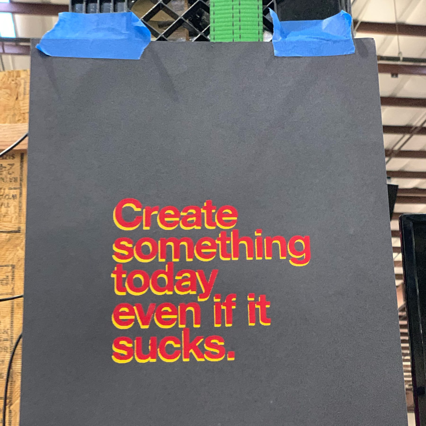 A letterpress-printed poster reading 'Create something today, even if it sucks.'