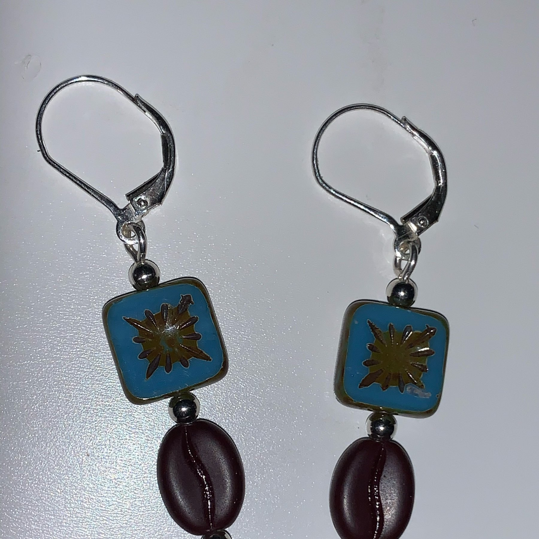 A pair of earrings each having a blue, square bead and coffee bean bead mounted on silver