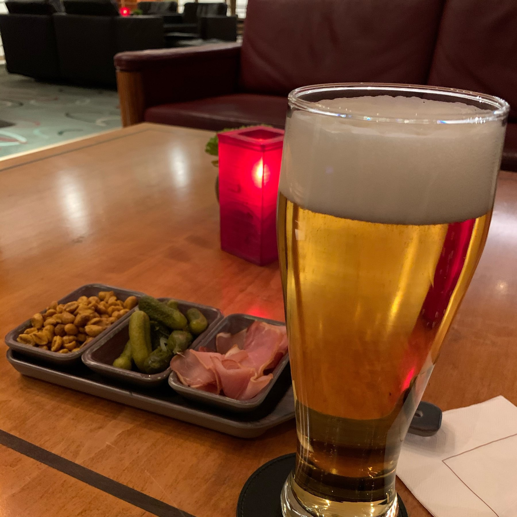 a large glass of pilsner with a tray of snacks behind it