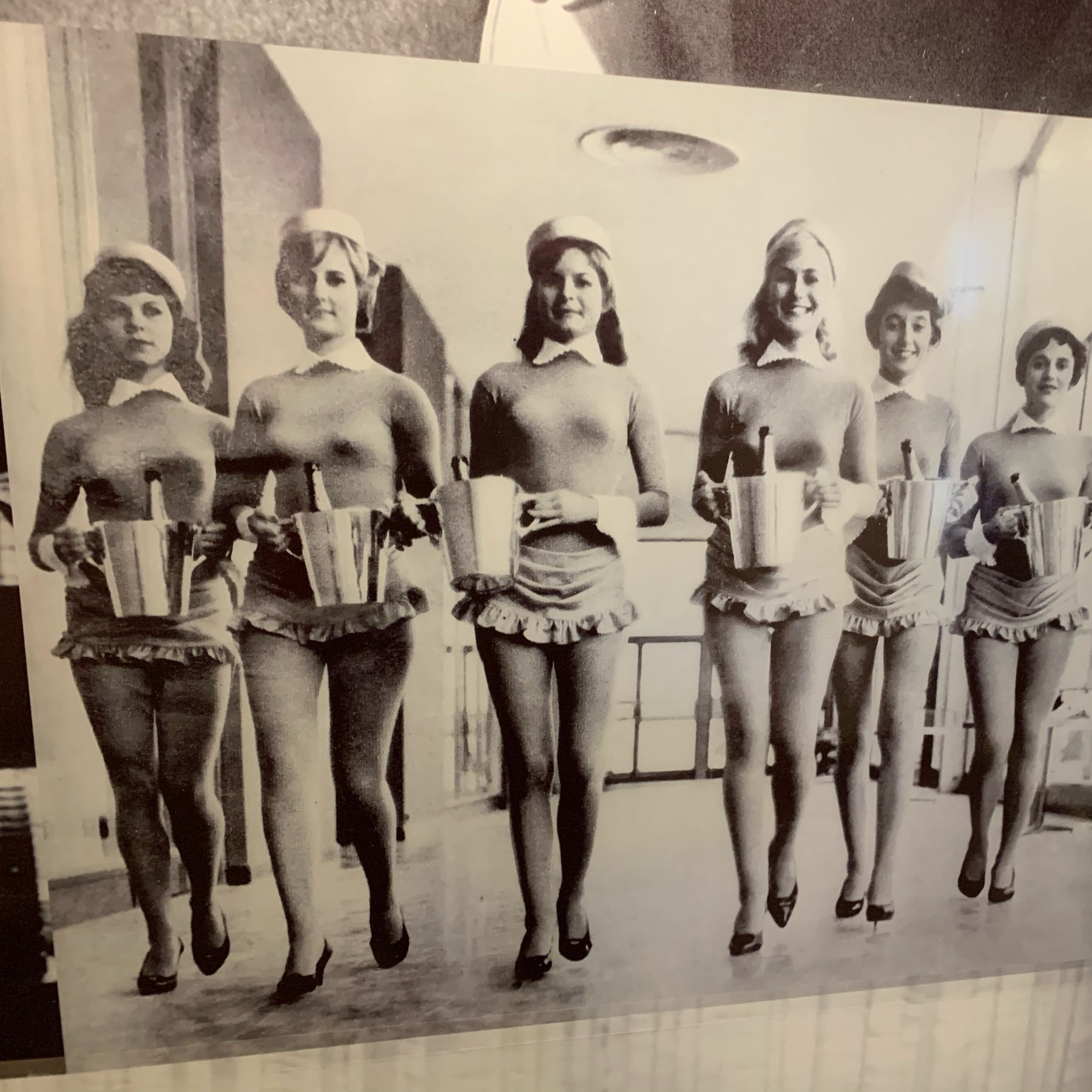 A photo of staff from the Berlin Intercontinental Hotel wearing a catsuit, maid's hats, and a skirt-like thing, all carrying buckets with bottles of champaign