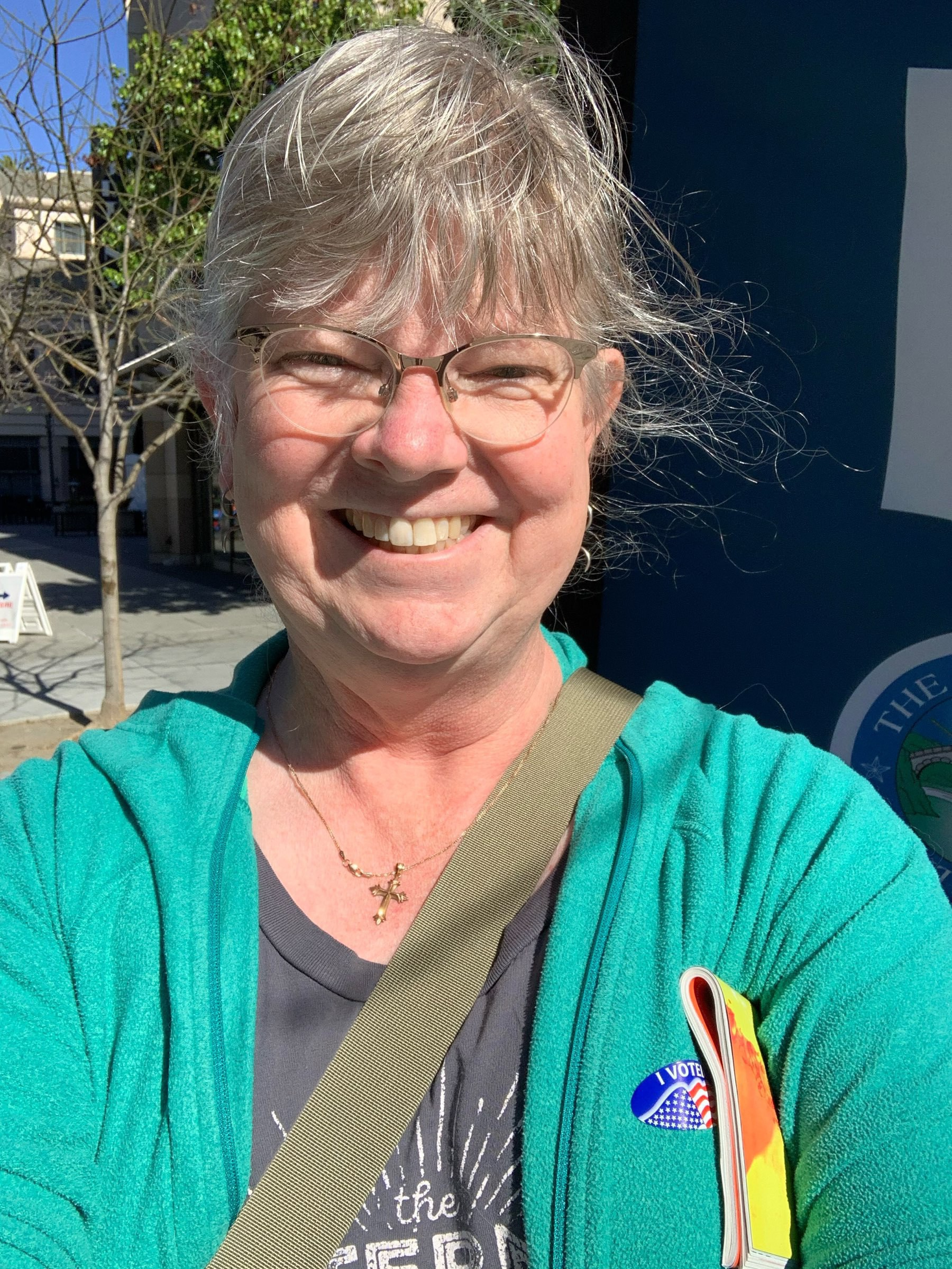"""Smiling blonde white woman with glasses and windblown hair wearing a green jacket with an """"I Voted"""" sticker."""
